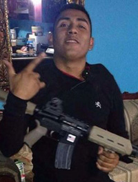 cartel idiot showing a gang sign, a large weapon and an IQ of 60.