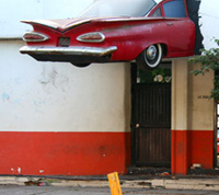 street photo of a '62 Chevy hanging from the side of the Yardas Strip Club in Culiacan