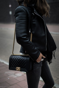 model wearing black leather pants, jacket and designer handbag from Leon