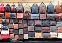 a wall of leather purses and handbags in different colors and sizes