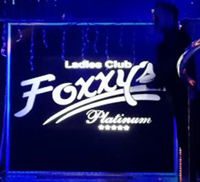 blue neon sign with white letters for Foxxy's Strip Club in Merida