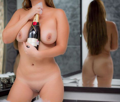 Miranda cradling a bottle of champagne between her big naked breasts