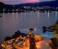 The Zihuatanejo harbor at sunset, with pink clouds and beautiful resort lights